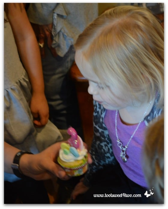 Blowing out candle on cupcake