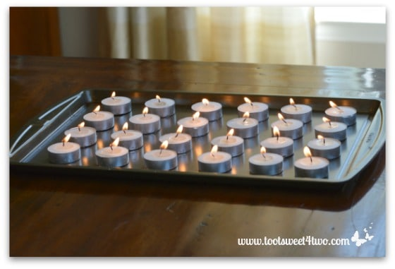 Lit tea lights on cookie sheet