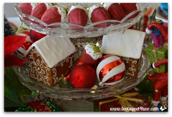 Gingerbread house candles and strawberry ornaments on a 3-tier dessert stand