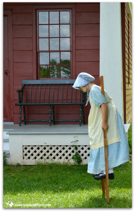 Stilt walker in front of Land Office at Genesee Country Village