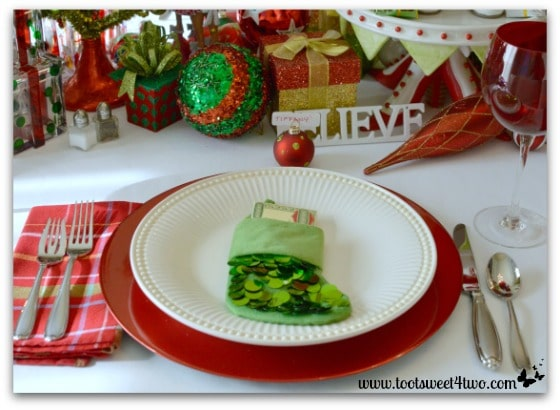 Christmas table place setting with green Christmas stocking