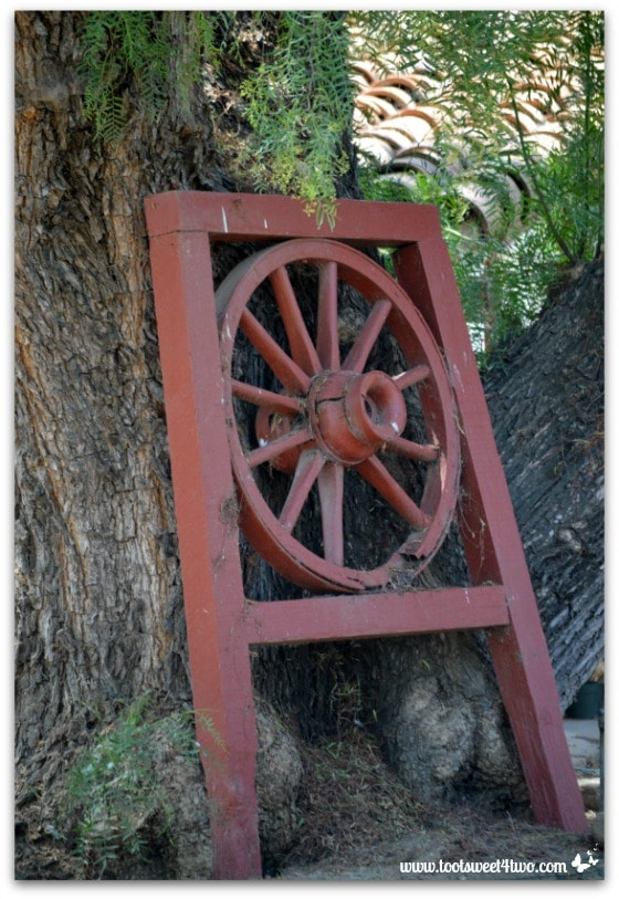 Framed wagon wheel against a tree in the gardens of Mission San Antonio de Pala