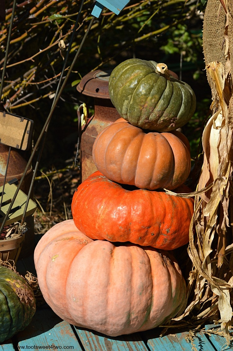 Leaning pumpkins stacked on a porch