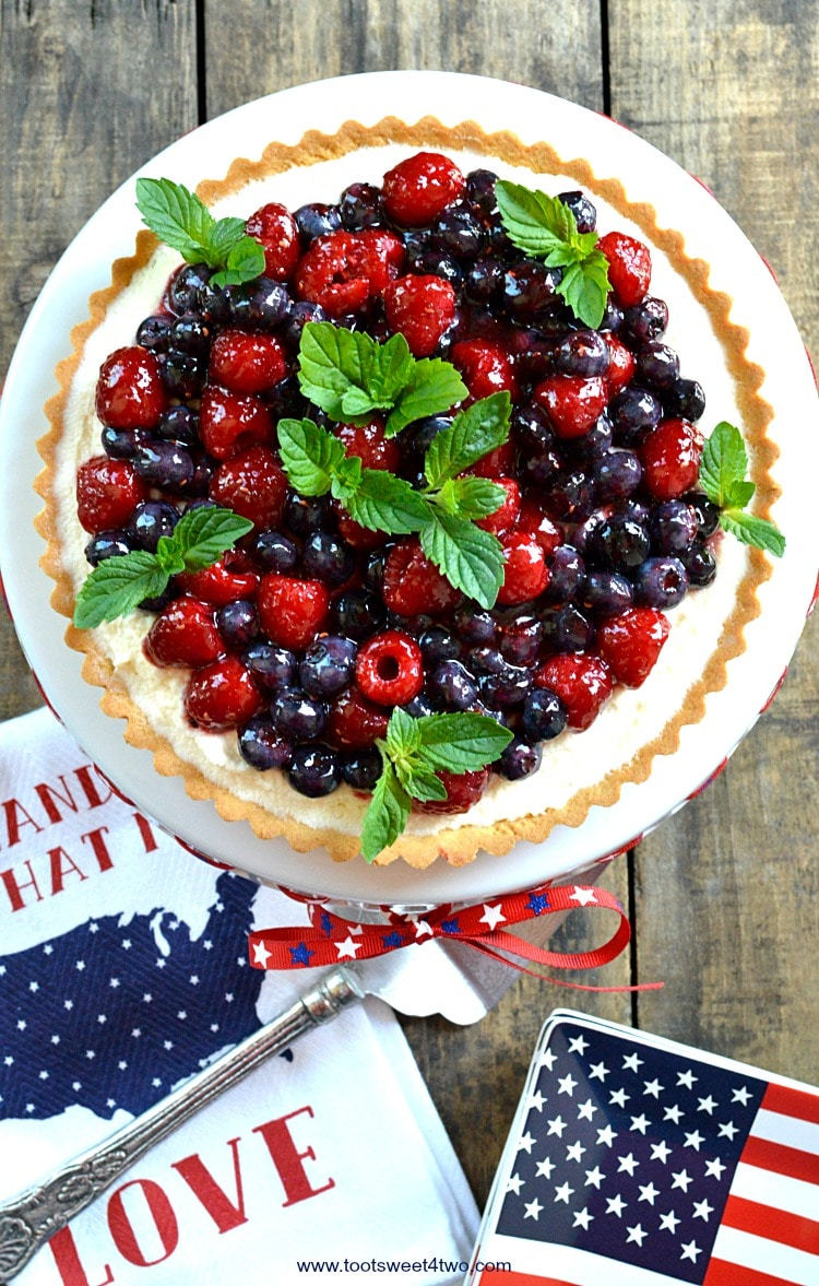 An easy, no-bake dessert, Patriotic Summer Berry Double-Cream Tart is a winning recipe to celebrate 4th of July or any red, white and blue holiday. A flaky, store-bought sweet pastry tart shell covered with a sweet double-cream filling and topped with fresh fruit, makes a beautiful and delicious treat for Independence Day! | www.tootsweet4two.com