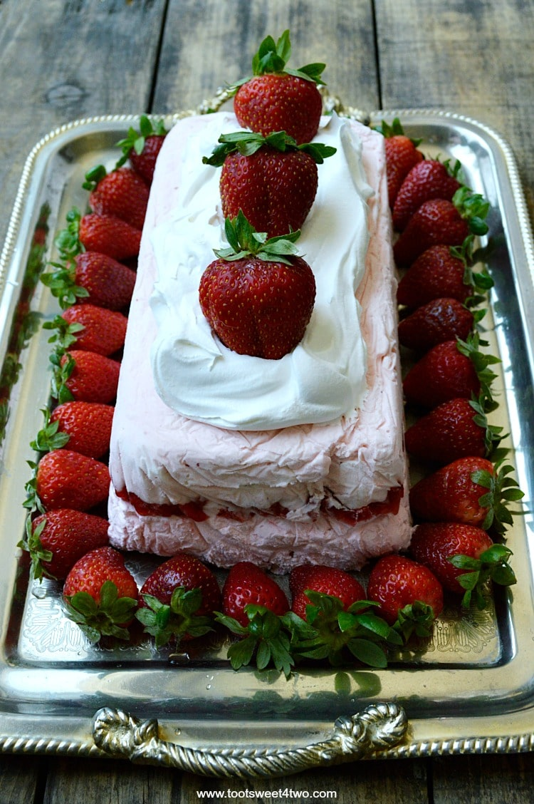 """Looking for unique cheesecake recipes? Look no further! Strawberry Icebox Cheesecake is an easy, frozen, no bake strawberry cheesecake dessert that combines an easy-to-make strawberry cheesecake layer with a layer of strawberry cheesecake ice cream. Frozen for hours or overnight, unmold this luscious concoction onto a pretty platter, dollop with Cool Whip and then top with fresh strawberries. A spectacular-looking dessert, this delicious recipe will """"wow"""" friends and family. 