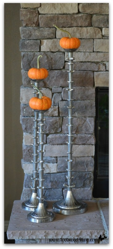 Mini pumpkins on candlesticks on hearth