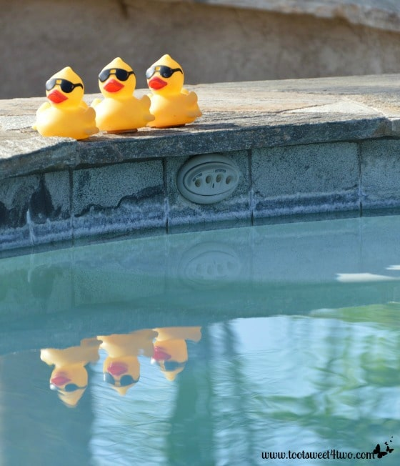 Yellow duckies with sunglasses reflected in the pool