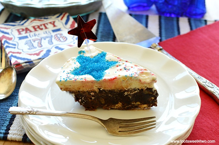 Firecracker Brownie Pie - a fun and festive 4th of July brownie recipe made with store-bought chocolate fudge brownie mix. Jarred hot fudge topping, vanilla ice cream and a surprise ingredient make this easy Independence Day dessert worthy of any Patriotic party celebration! Add sparkly red and blue stars by using various size star-shaped cookie cutters! | www.tootsweet4two.com