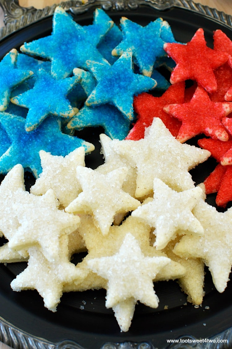 Firecracker Pie Crust Stars - made with store-bought pre-made pie crust dough cut-out with various star-shaped cookie cutters, slathered with butter then liberally sprinkled with colored sugar and baked, these cookies are the perfect sweet/salty combo that's so addicting! Get this easy and festive 4th of July Patriotic party recipe at www.tootsweet4two.com.