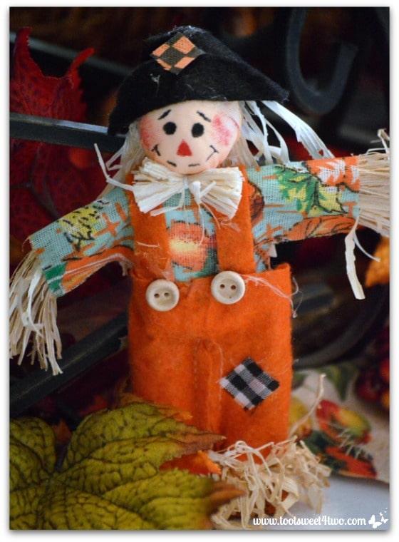 Miniature scarecrow in orange overalls