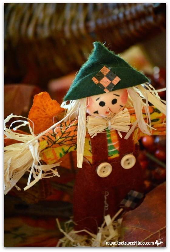 Miniature scarecrow in rust overalls