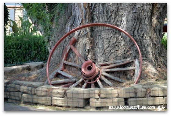 Old wagon wheel at base of tree at Mission San Antonio de Pala