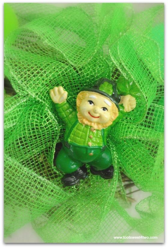 Leprechaun nestled in green ribbon