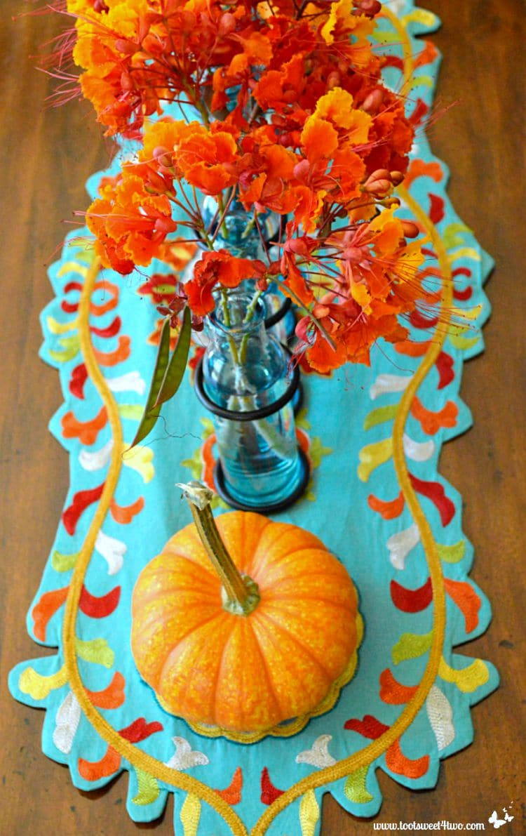 Turquoise table runner with mini pumpkin and Red Mexican Bird of Paradise