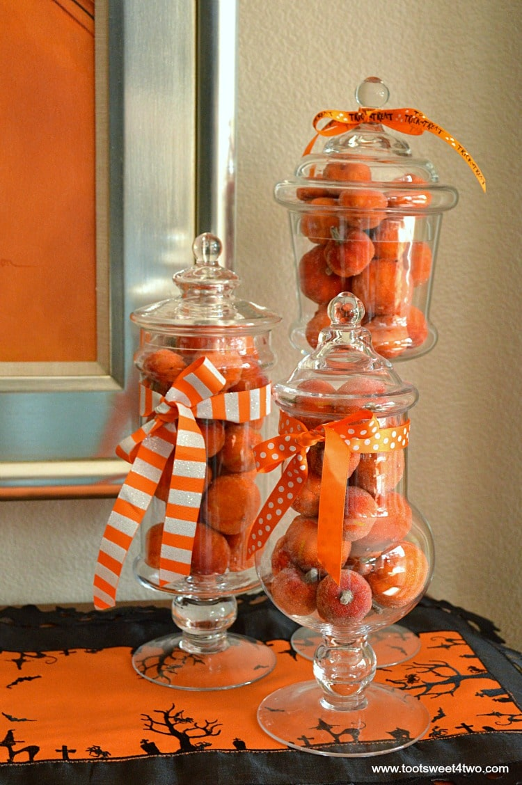 Mini faux pumpkins stacked inside glass jars