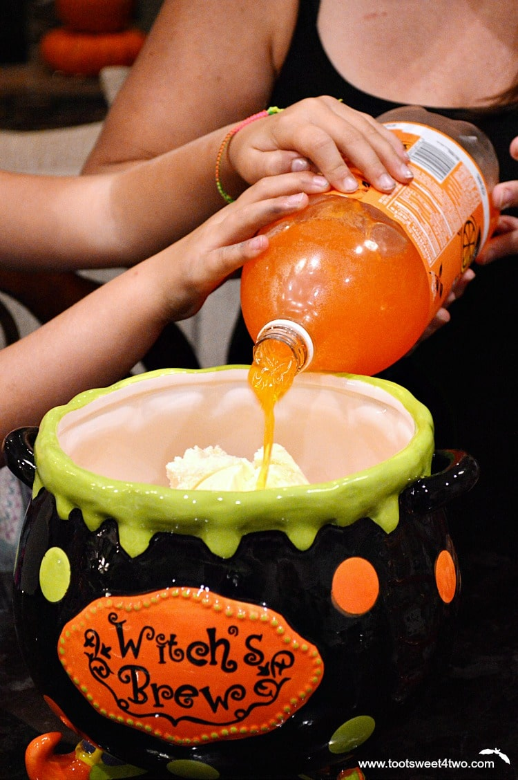 Pouring orange soda over vanilla ice cream