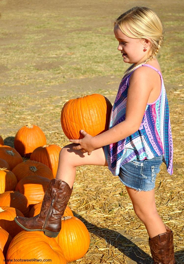 Princess Sweetie Pie hoisting a pumpkin on her knee