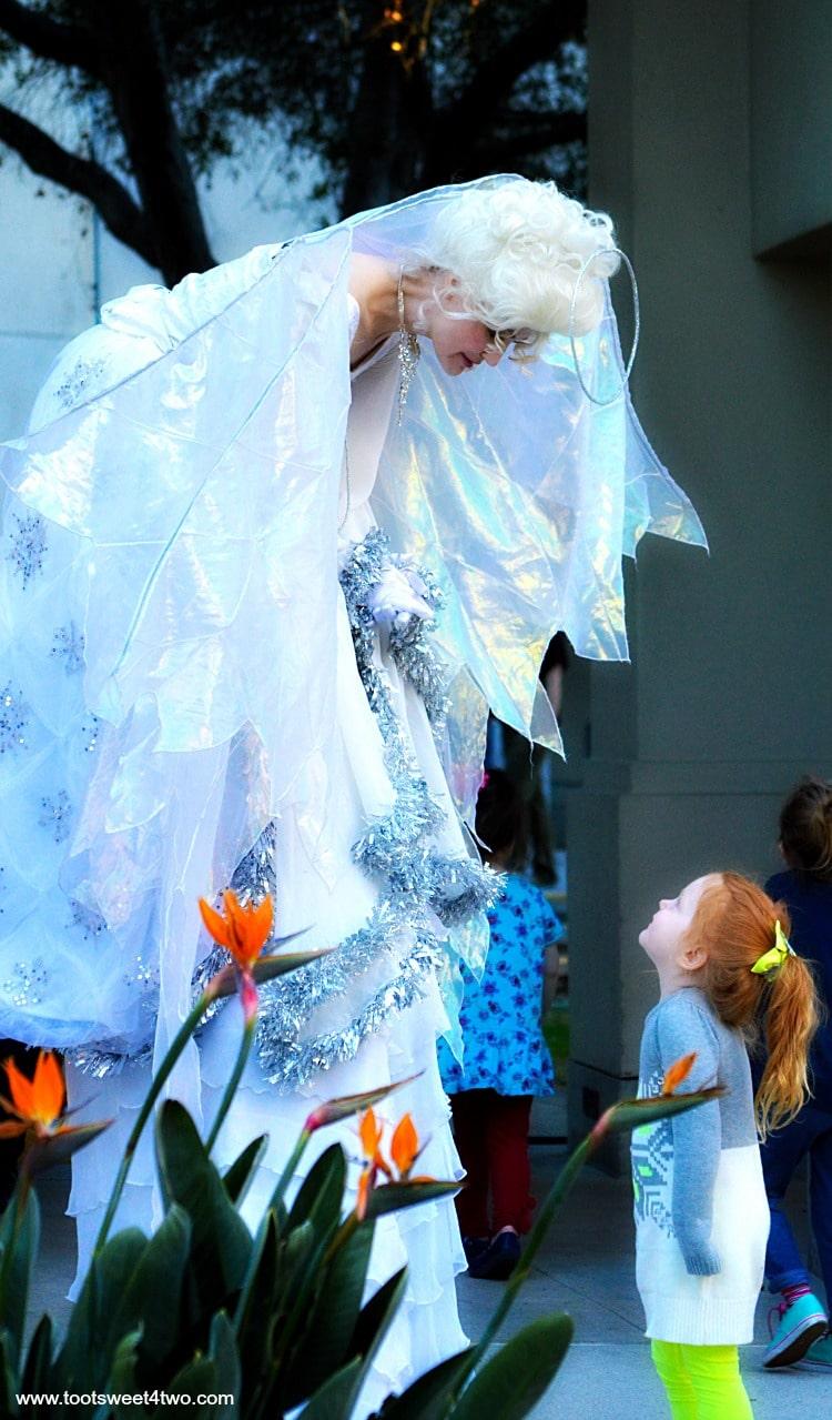 Angel stilt-walker talking to little red-headed girl