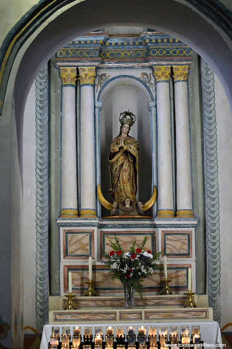 Statue of Mary in candle altar inside Mission San Luis Rey Church