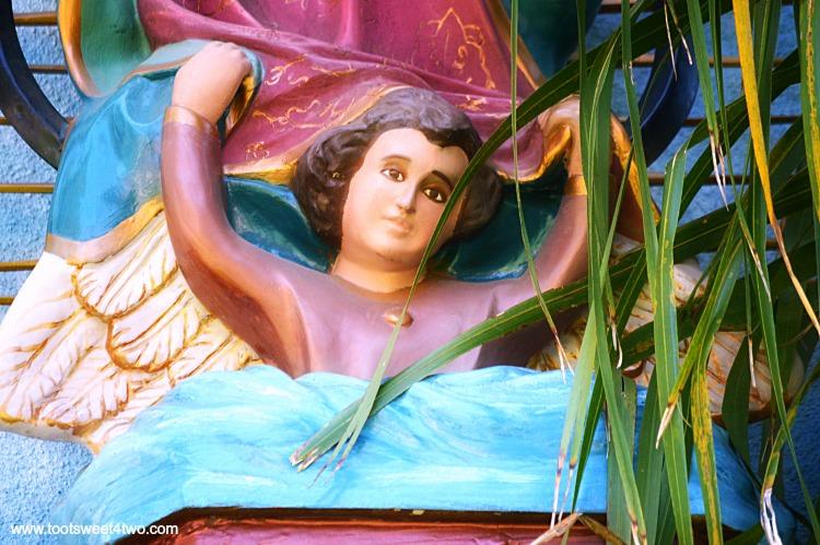 Angel holding up Madonna on side of building at Old Mission San Luis Rey Gardens