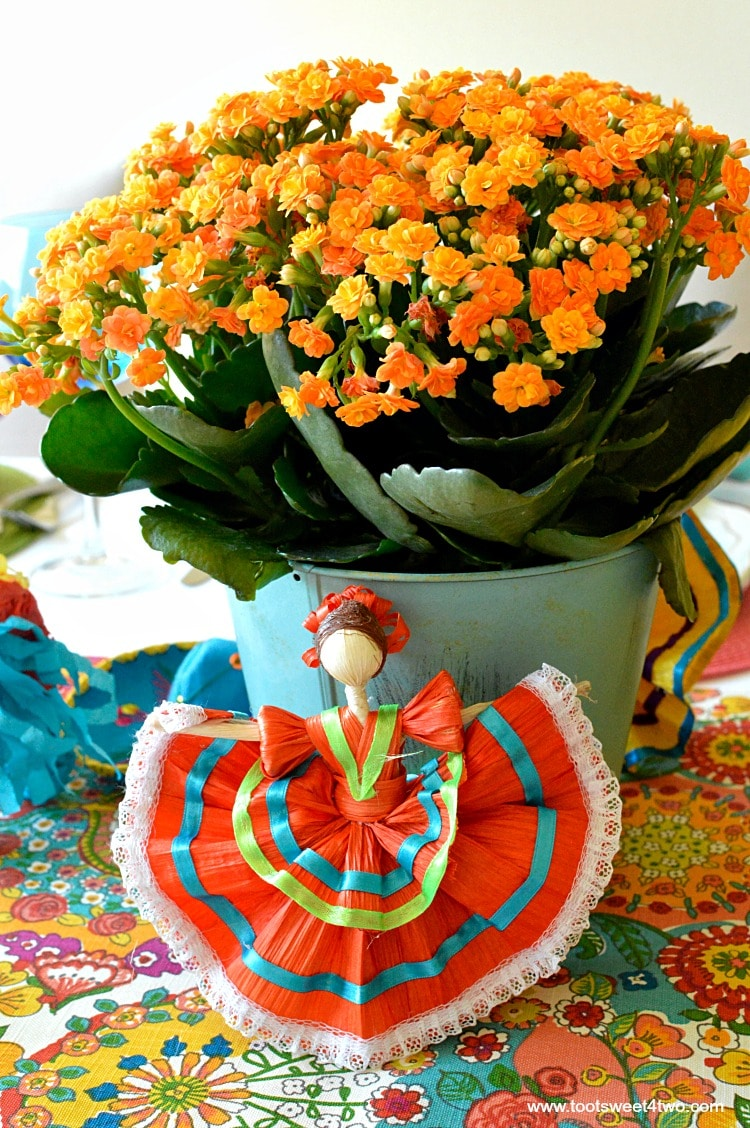 Orange Kalanchoe flowers and orange corn husk doll for Decorating the Table for a Cinco de Mayo Celebration