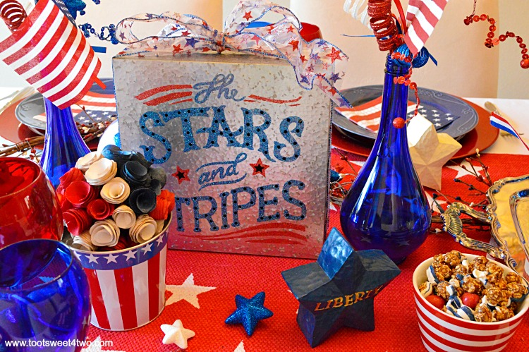 Decorating the table for a 4th of July party? Decked out in red, white and blue, this table scape has a Patriotic centerpiece mimicing fireworks with stars and stripes galore. Check out the decorations and ideas for your Independence Day celebration at www.tootsweet4two.com.