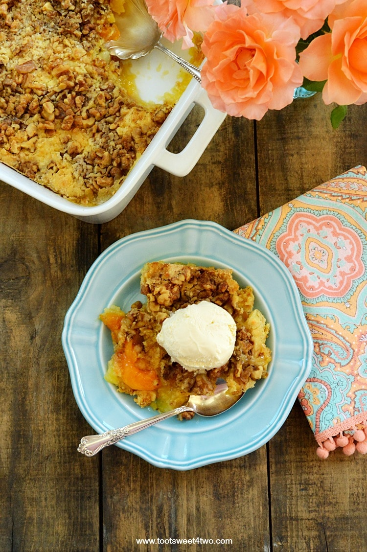 How to make dump cake? There's really no lesson involved! Most dump cake recipes don't even require a bowl! Using pie fillings and cake mix plus a few other ingredients, just open a couple of cans and a box, dump them in a baking dish and bake! Simple and easy, Peach Pineapple Dump Cake with Walnuts is one of the most delicious desserts of all time! | www.tootsweet4two.com